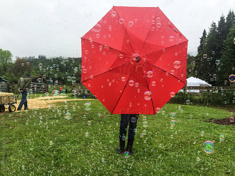 Bubble Machine, Red Umbrella  by Ryan Matthew Smith for Stocksy United