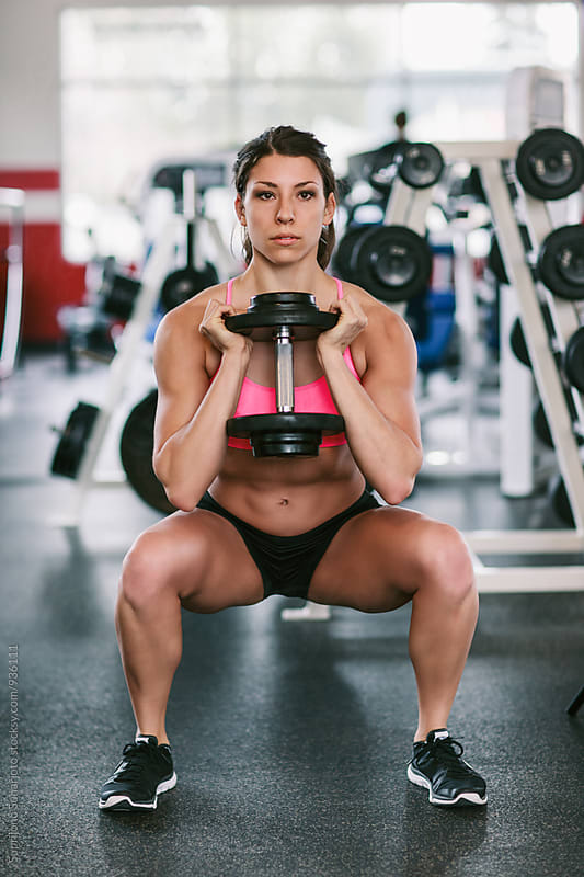 Woman working out doing squat with dumbbell in the gym  by Suprijono Suharjoto for Stocksy United