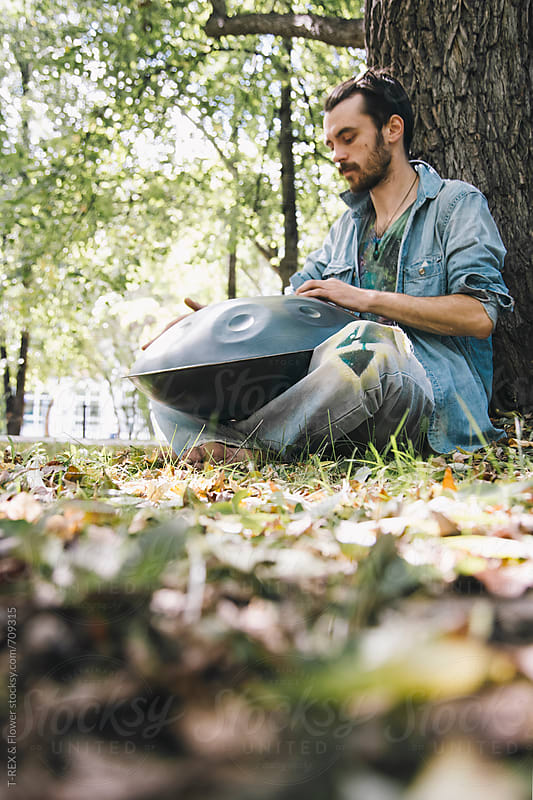 Man playing hang drum in the park by Danil Nevsky for Stocksy United