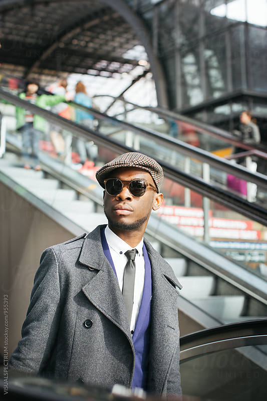 Stylish Young Black Businessman With Sunglasses Coming Up Escalator by VISUALSPECTRUM for Stocksy United