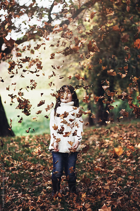 Young child surrounded by autumn leaves by Jovana Rikalo for Stocksy United