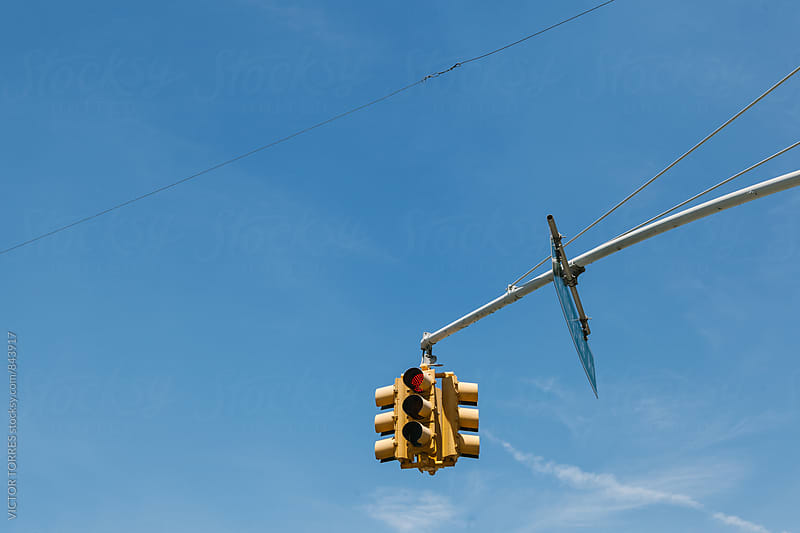 Yellow Traffic Light Against a Blue Sky by VICTOR TORRES for Stocksy United