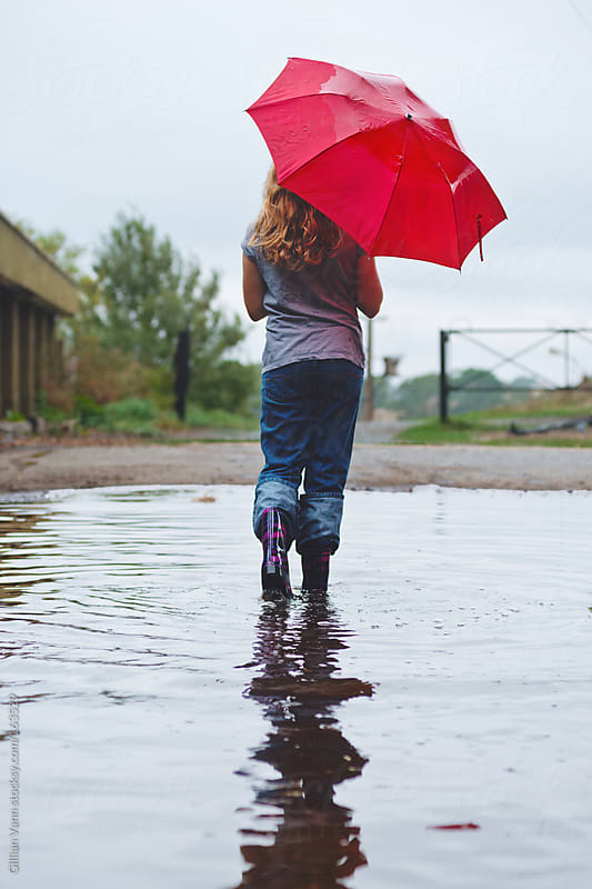 girl walking through puddle with umbrella by Gillian Vann for Stocksy United