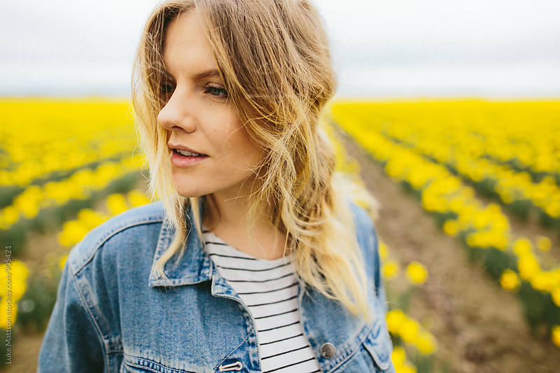 Portrait Of Young Blonde Woman In Field Of Daffodils by Luke Mattson for Stocksy United
