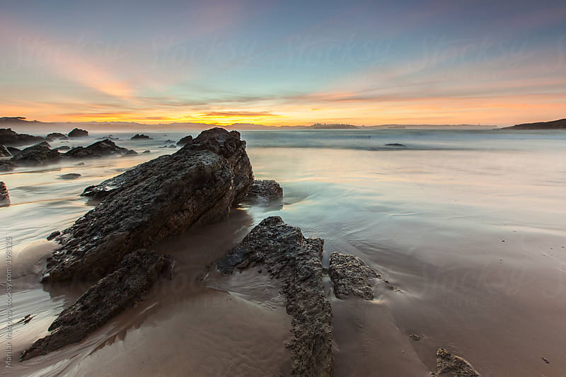 Sunset on a rocky beach in front of Santander by Marilar Irastorza for Stocksy United