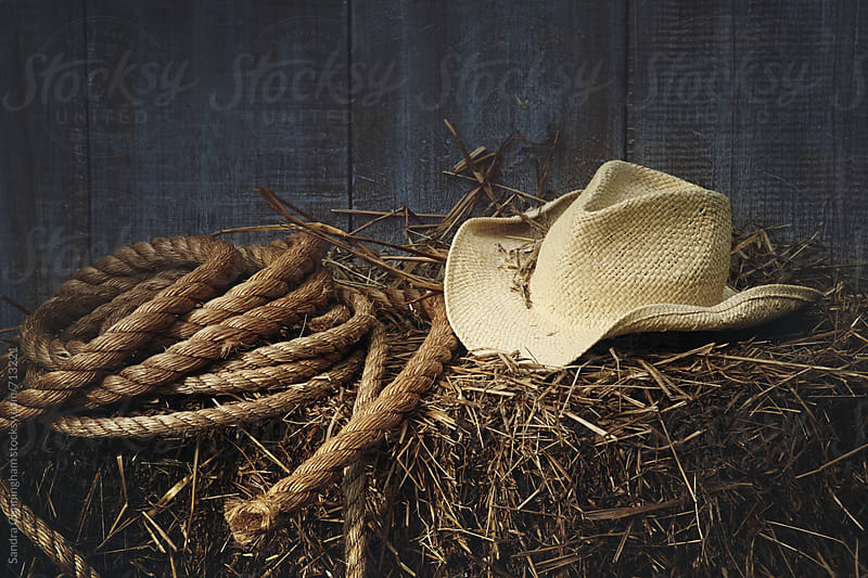 Western straw hat on a bale of hay by Sandra Cunningham for Stocksy United