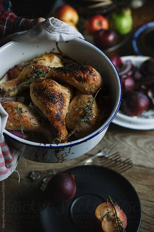Roasted chicken in a pot being served onto a table. by Darren Muir for Stocksy United