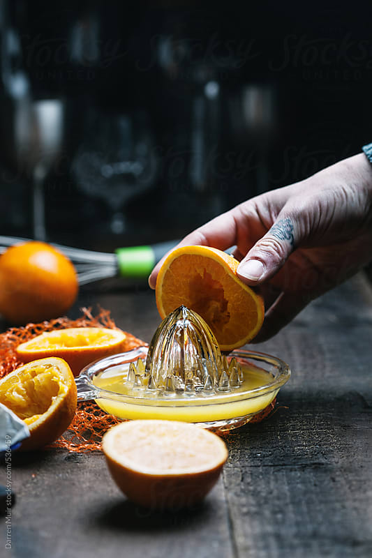 Woman's hand squeezing orange's in a glass juicer. by Darren Muir for Stocksy United