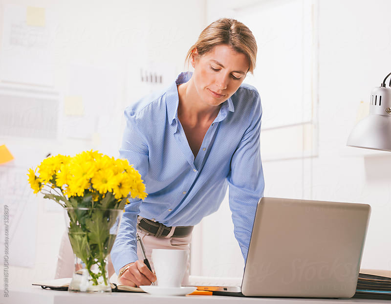 Beautiful mature business woman working with laptop at home office. by BONNINSTUDIO for Stocksy United