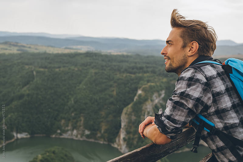 Man with backpack looking at nature from a view point by Jovo Jovanovic for Stocksy United