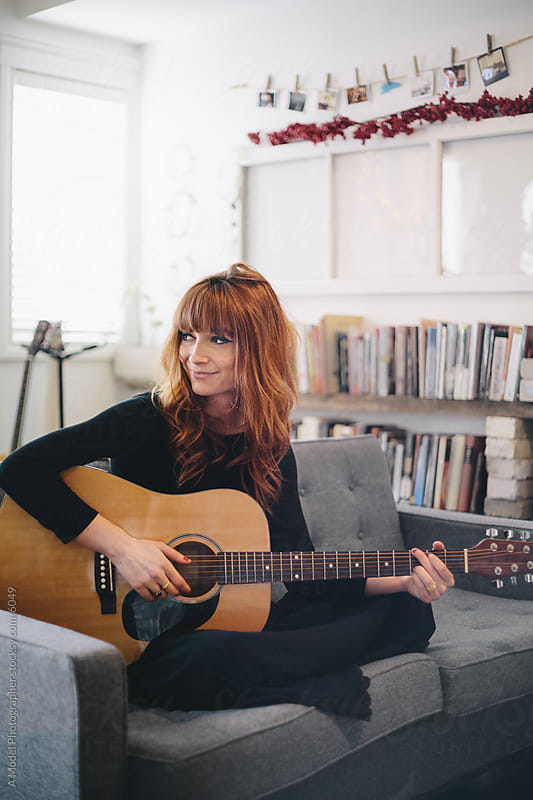 A portrait of a young woman playing guitar by Ania Boniecka for Stocksy United