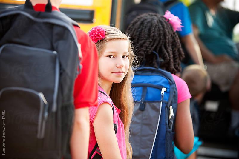 School Bus: Schoolgirl in Line Looks Back by Sean Locke for Stocksy United
