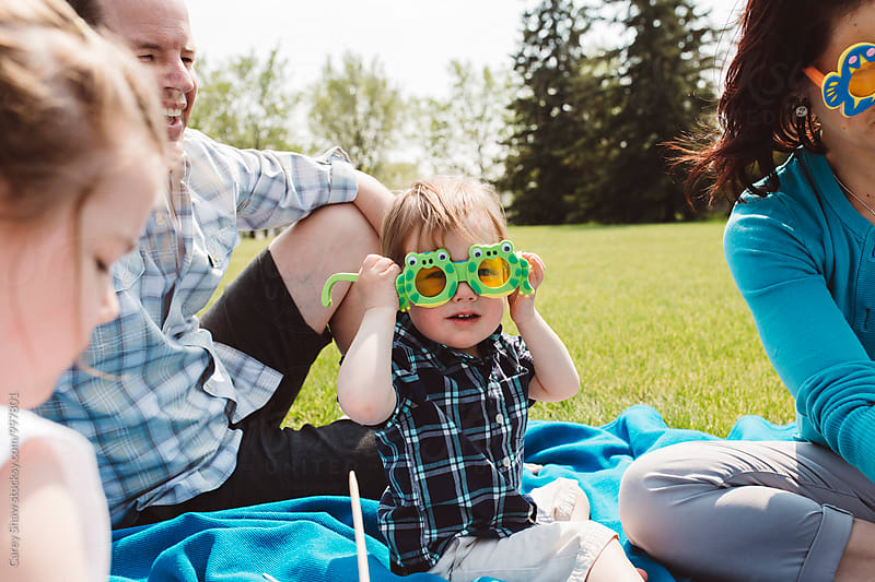 Boy wearing funny glasses, sitting with his family by Carey Shaw for Stocksy United