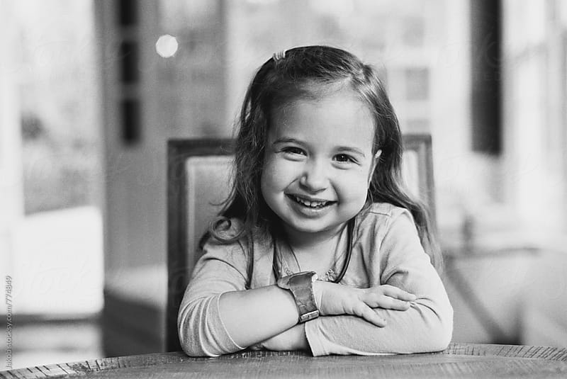 Portrait of a happy young girl at a kitchen table by Jakob for Stocksy United