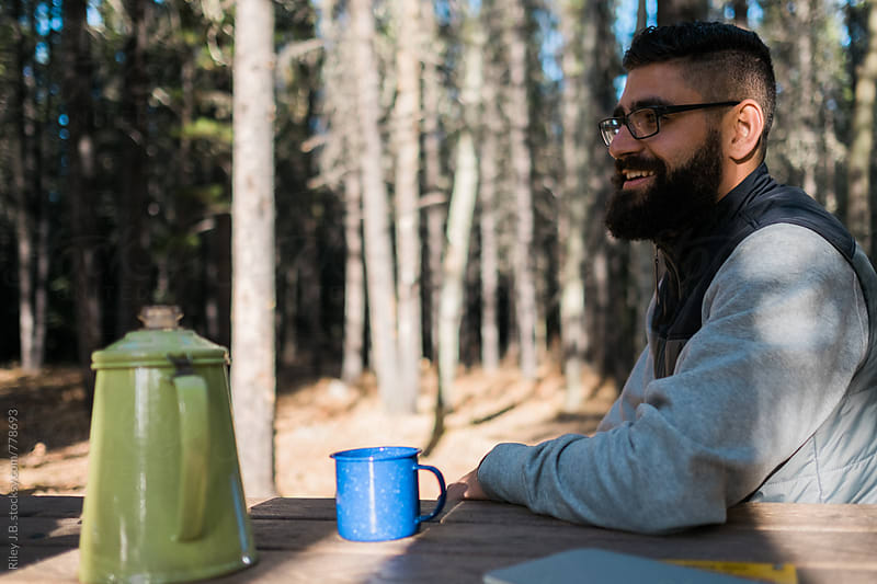 A bearded man smiles while sitting at a picnic table with enameled mugs and a kettle. by Riley J.B. for Stocksy United