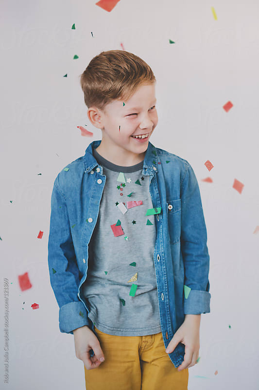 Laughing as holiday confetti falls down by Rob and Julia Campbell for Stocksy United