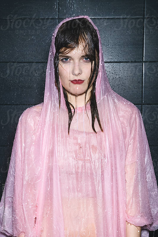 Woman taking shower in pink raincoat  by T-REX & Flower for Stocksy United