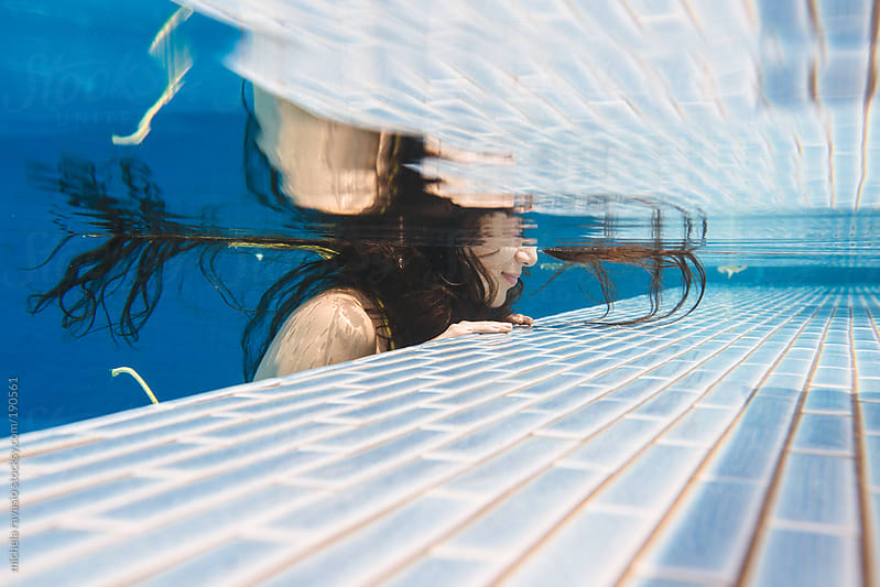 Woman resting on the edge of swimming pool, underwater view. by michela ravasio for Stocksy United