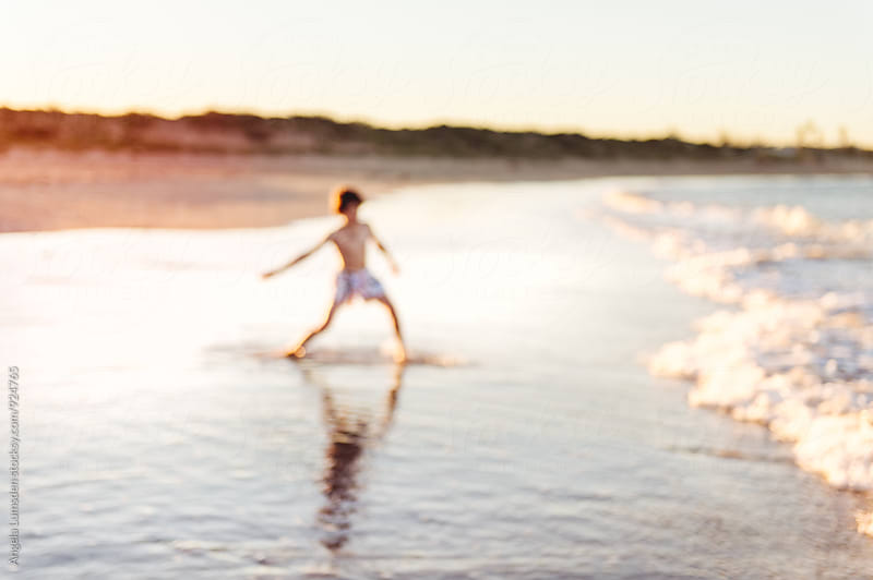 Boy playing in low waves at the beach at sunset by Angela Lumsden for Stocksy United