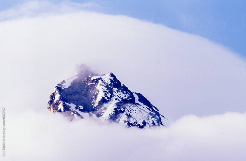 telephoto of clouds enveloping the summit of Mt Hood in Oregon by Ron Mellott for Stocksy United