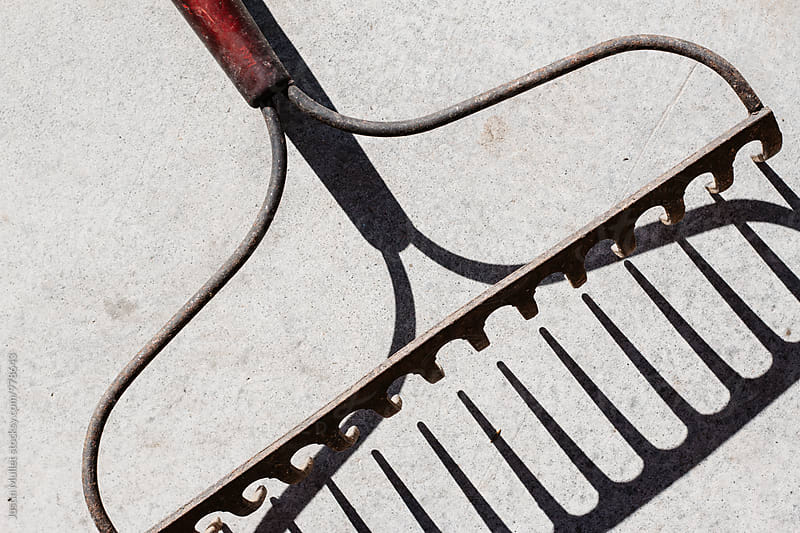 Close up of garden rake and shadow on concrete floor by Justin Mullet for Stocksy United