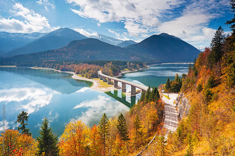 Reflections of a road bridge over Lake Sylvenstein, with mountains in the background, in Bavaria, Germany by Gavin Hellier for Stocksy United