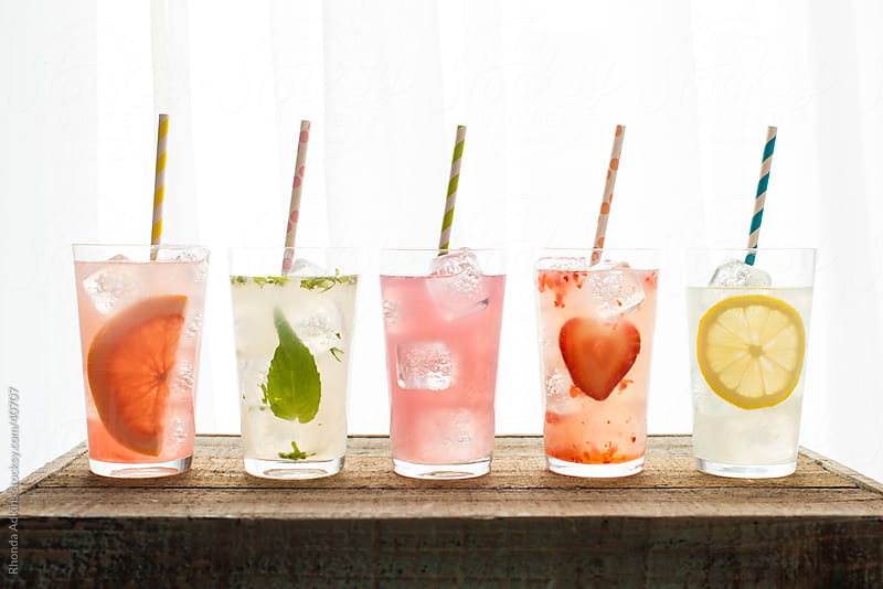 Five varieties of lemonade with colored straws by Rhonda Adkins for Stocksy United