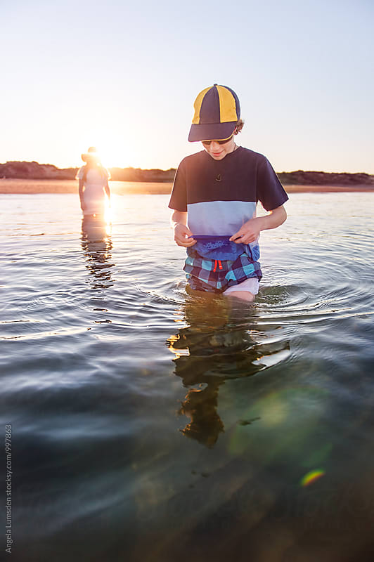Children playing in calm water at sunset by Angela Lumsden for Stocksy United