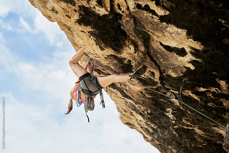Unrecognizable woman in climbing gear ascending the cliff by Guille Faingold for Stocksy United