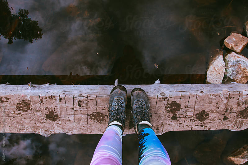 Hiking on a bridge over water by Abby Mortenson for Stocksy United
