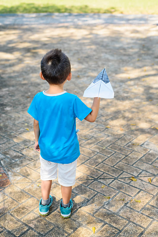 Little boy holding paper airplane by Lawren Lu for Stocksy United