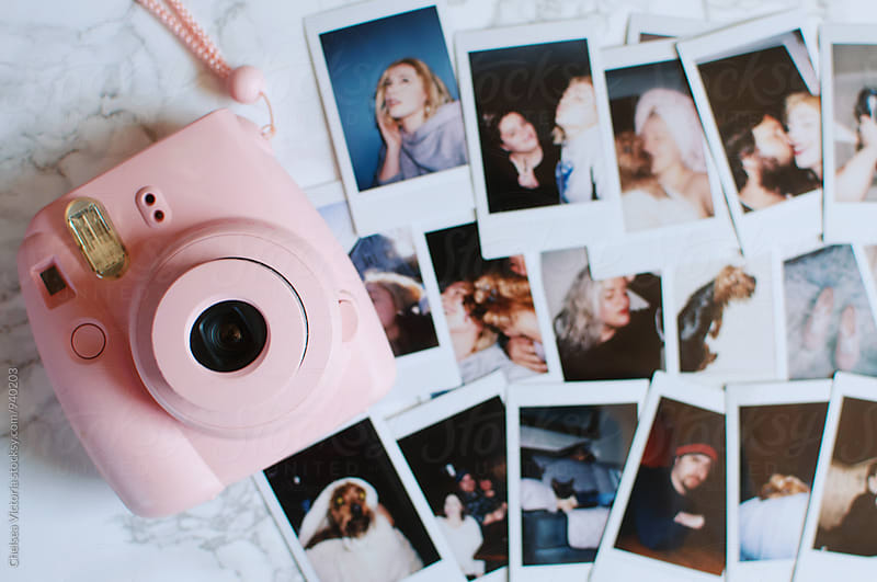 A pink camera and polaroid photographs by Chelsea Victoria for Stocksy United
