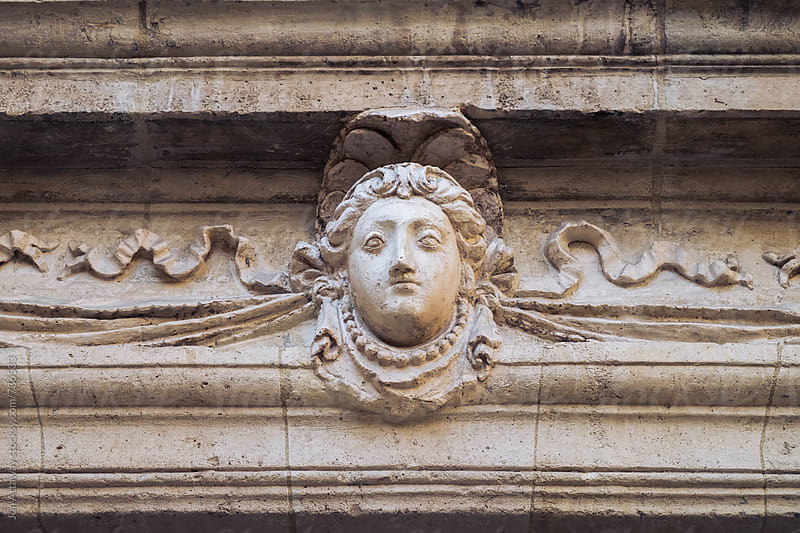 Detail of a head sculpture on a building by Jon Attaway for Stocksy United