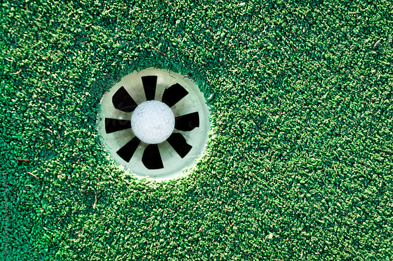 overhead view of a golf ball in the hole by Gillian Vann for Stocksy United