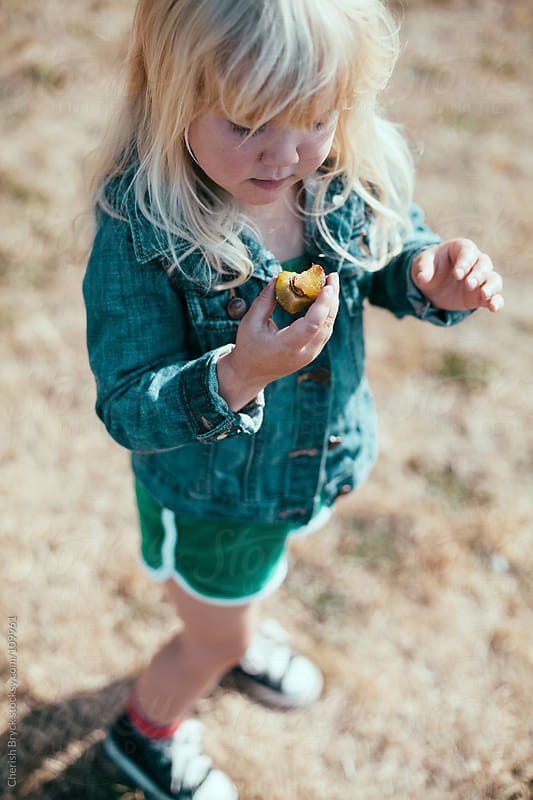 A little girl stands and eats a fresh plum. by Cherish Bryck for Stocksy United