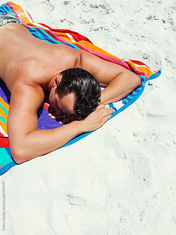 Man Tanning on the Beach by Taylor Kampa for Stocksy United
