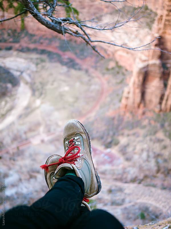 Feet Dangling Off The Edge Of A Cliff by Laura Austin for Stocksy United