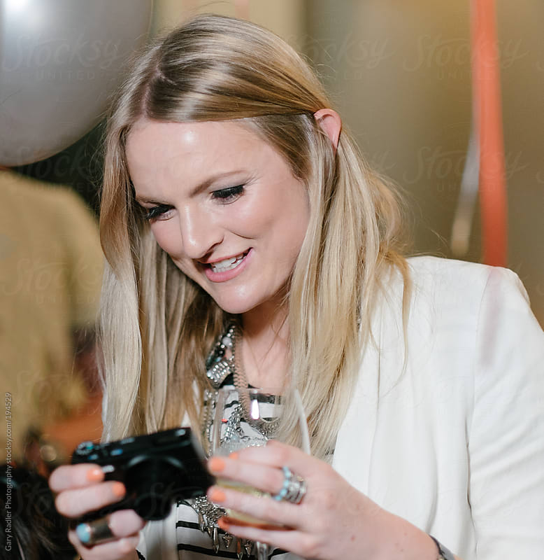 Young Woman Looking at Back of Compact Camera at a Party by Gary Radler Photography for Stocksy United