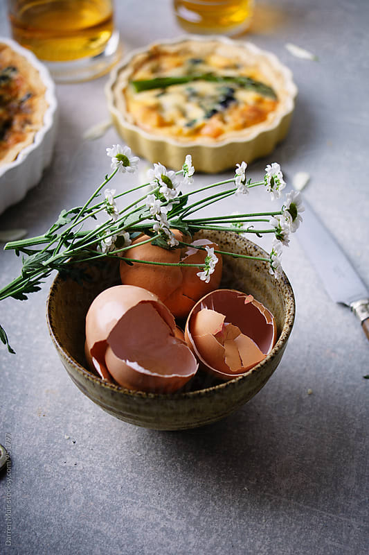 Egg shells and flowers in a stoneware bowl. by Darren Muir for Stocksy United