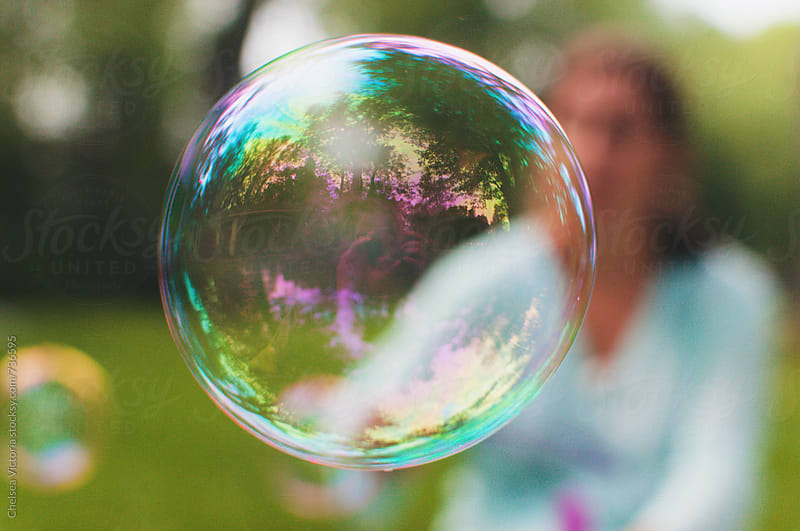 A woman blows bubbles by Chelsea Victoria for Stocksy United