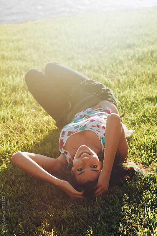 Flirtatious hot girl lying on her back on a grassy lawn looking up by paff for Stocksy United