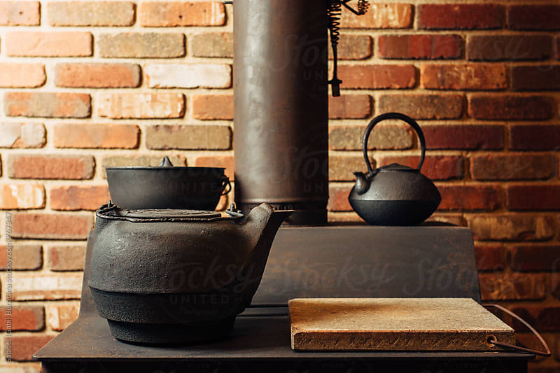 Cast iron teapots on a wooden stove by Gabriel (Gabi) Bucataru for Stocksy United