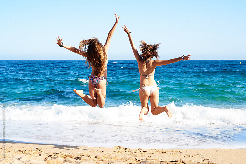 Back view of girls in bikini jumping on beach by Guille Faingold for Stocksy United