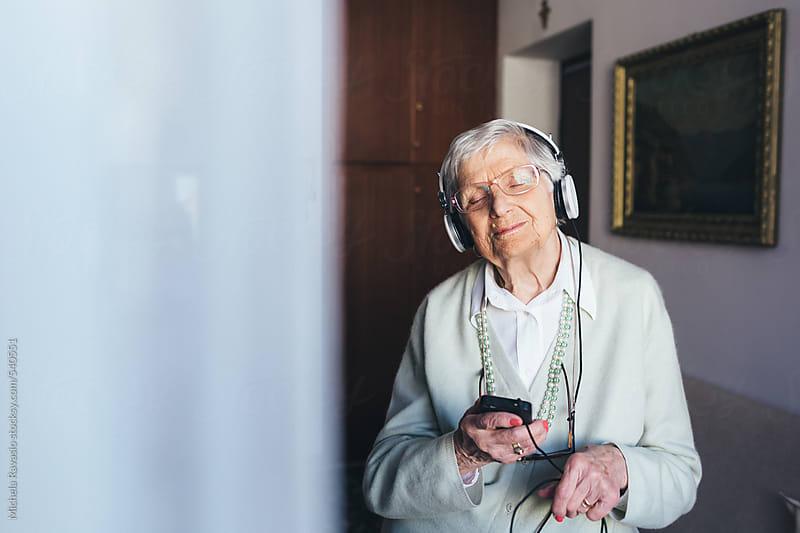 Elderly woman listening to music by michela ravasio for Stocksy United