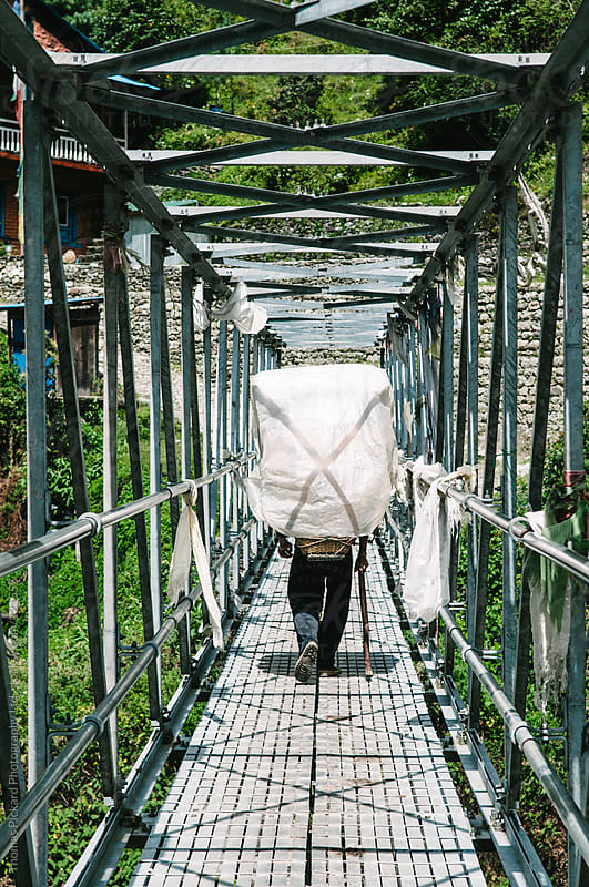 Sherpa carrying a load across a bridge, Lukla Valley, Everest Region, Sagarmatha National Park, Nepa by Thomas Pickard Photography Ltd. for Stocksy United