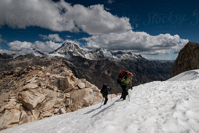 Mountain climbers on glaciated slope with mountains behind by Mick Follari for Stocksy United