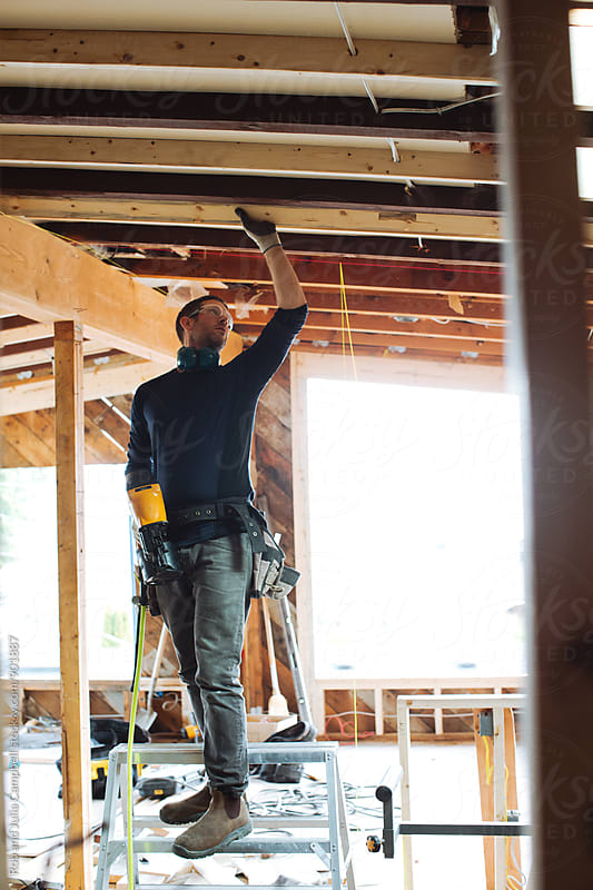 Building contractor using nail gun by Rob and Julia Campbell for Stocksy United