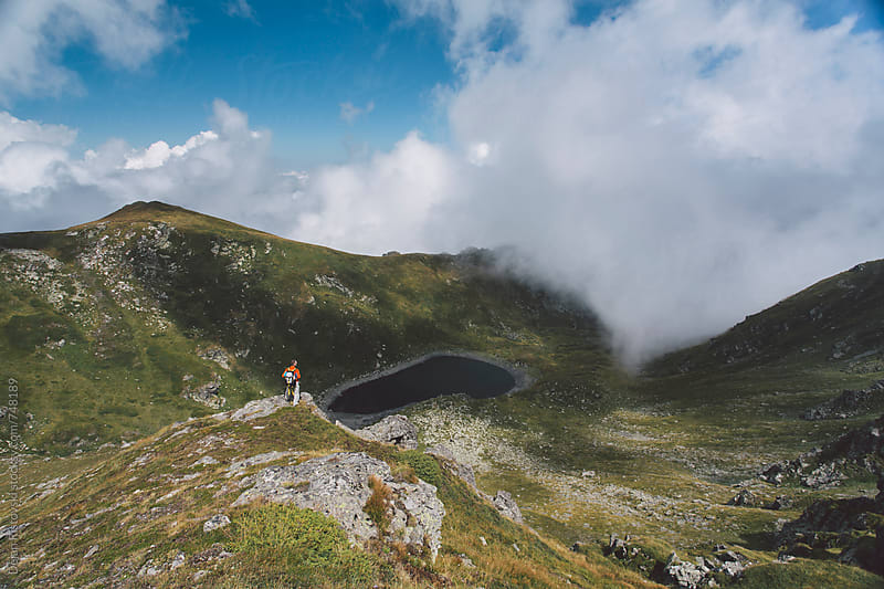 Hiker on peak on a beautiful mountain range by Dejan Ristovski for Stocksy United