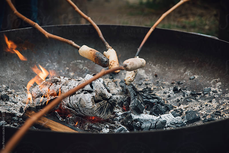 Food: Campfire Bread baked on sticks over the fire by Ina Peters for Stocksy United