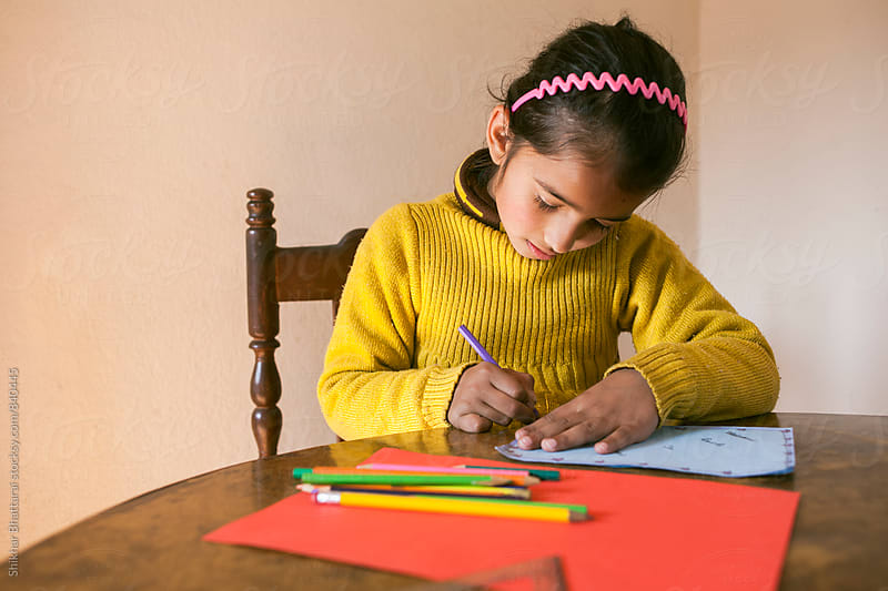 A young child sitting on a desk and making holiday cards. by Shikhar Bhattarai for Stocksy United